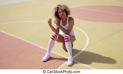 Attractive female athlete sits on basketball - Attractive...
