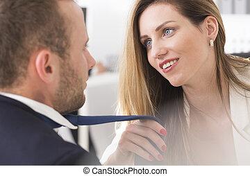 Attractive female boss grabbing co-workers tie