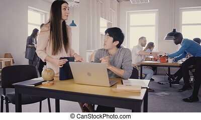 Attractive female boss listens to Asian colleague. Happy mixed ethnicity business people work in light office space 4K.