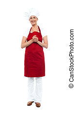 Attractive female chef in red apron and toque