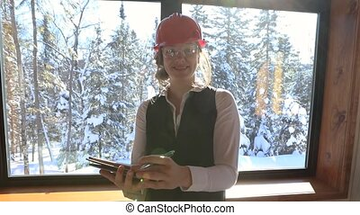home inspector happy woman standing on the front of a glass window with sun rays and snowy trees outside as she smiling and holding a clipboard.
