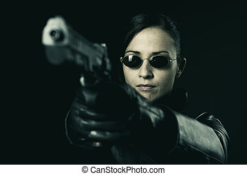 Attractive female criminal pointing a gun
