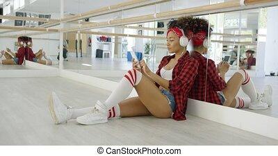 Attractive female dance student seated in studio