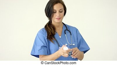 Attractive female doctor holding out a pill
