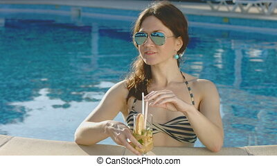Attractive female drinking cocktail, relaxing in pool. Vacation