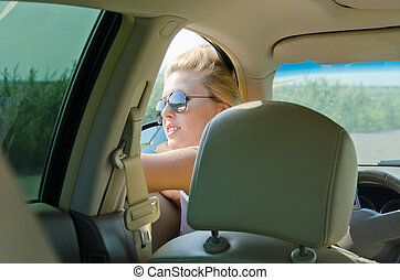 Attractive female driver looking through window of her car