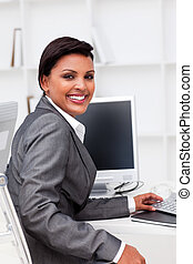 Attractive female executive working at a computer in the ...