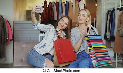 Attractive female friends are using smartphone to make selfie while sitting in clothing shop with colourful paper bags. They are smiling, posing, laughing, gesturing.