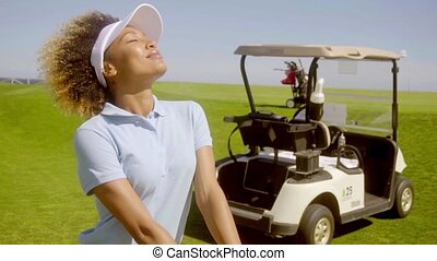 Attractive female golfer with a golf cart - Attractive...