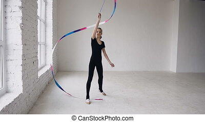 Attractive female gymnast dancing with ribbon in gymnastics school at white background and look at the camera. Rhythmic gymnast