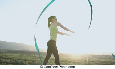 Attractive female gymnast dancing with ribbon in top of mountain at sunset background. Rhythmic gymnast. Sports girl