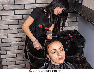 Attractive female hairdresser washing hair of young woman in washing sink