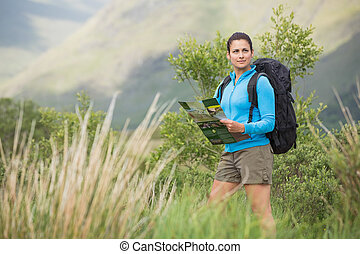 Attractive female hiker with backpack holding a map