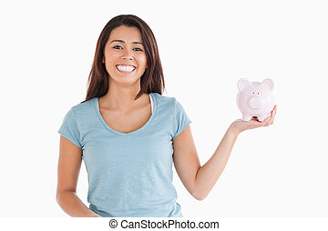 Attractive female holding a piggy bank