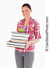 Attractive female holding and a apple and books while posing