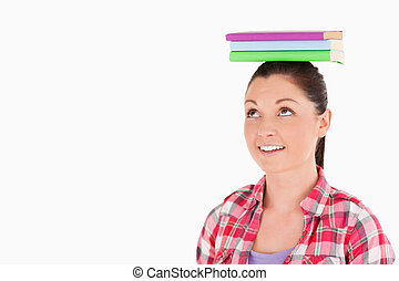 Attractive female holding books on her head while standing