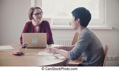 Attractive female leader listening to Japanese man at job interview. Lawyer woman consulting young handsome businessman.