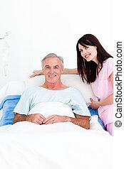 Attractive female nurse adjusting pillows for a senior patient