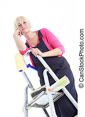 Attractive female painter posing on ladders isolated on...
