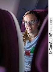 Attractive female passanger watching in-flight...