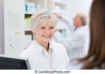 Attractive female pharmacist helping a patient - Attractive...