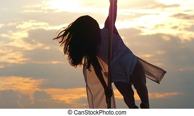 Attractive female pole-dancer rotating on the pole at sunset...