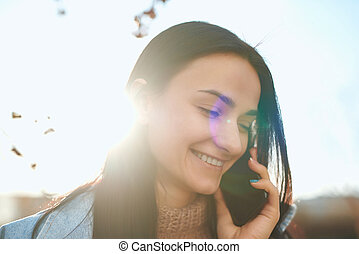 Attractive female posing with a cellphone in autumn sunlight