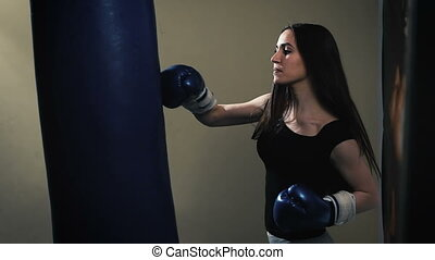 Attractive Female Punching A Bag With Boxing Gloves On....