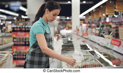 Attractive female saleswoman in apron is busy putting bags...