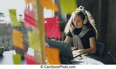 Attractive female student is listening to music with headphones dancing and singing while working with laptop computer. Glassboard with bright colored stickers in foreground.