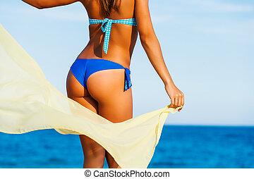 Attractive female suntanned body on beach. - Close up rear...