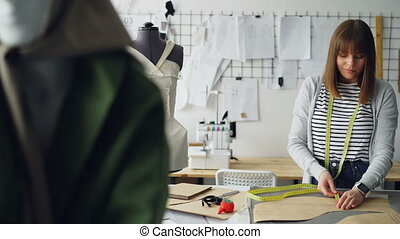 Attractive female tailor is measuring clothing patterns with...