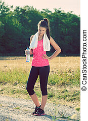 Attractive female taking a break after jogging, holding bottle of water