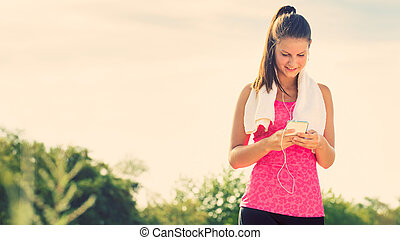 Attractive female taking a break during jogging, holding smartphone