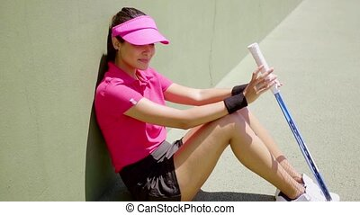 Attractive female tennis player sitting in the sun leaning...