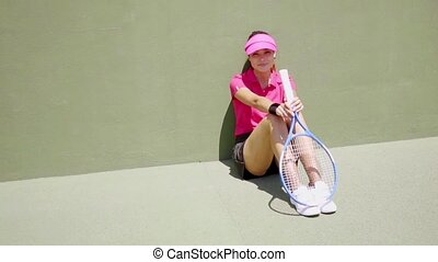 Attractive female tennis player sitting in the sun