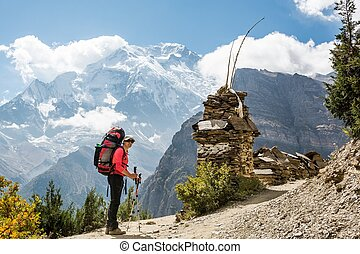 Attractive female trekker in front of the mountains.