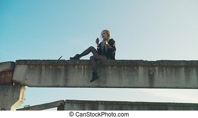 Attractive spooky female vampire with dreadlocks enjoying smell of fresh blood, drinking human blood from bottle while sitting on concrete beam in rays of warm setting sun in countryside.