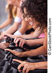 Attractive females on bicycles in a gym