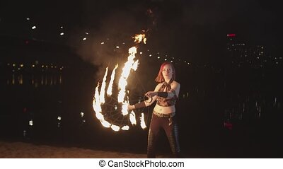 Attractive firegirl juggling spinning fans outdoor - Young...