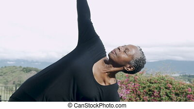 Attractive fit African American woman in 60s practicing yoga...