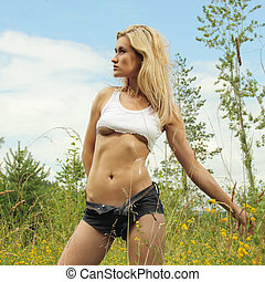 Attractive fitness model outdoors in shorts and torn shirt