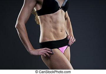 Attractive fitness woman on gray background in studio. Muscular abdomen close-up