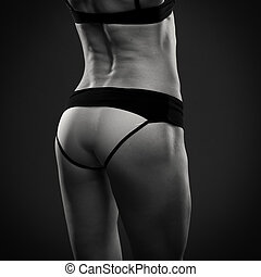 Attractive fitness woman on gray background in studio. Muscular buttocks close-up