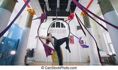 Attractive flexible women circling on the aerial hoop and silk in a studio