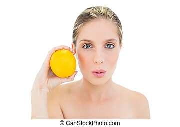 Attractive fresh blonde woman pouting and holding an orange