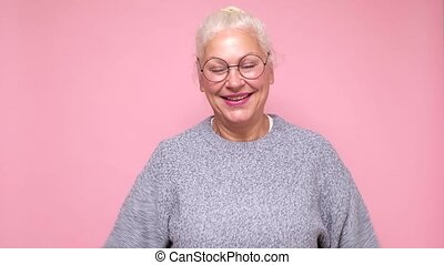 Attractive friendly senior woman smiling happily, saying Hello, Hi or Bye, waving hand. Studio shot on pink wall.