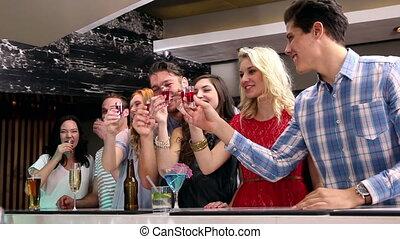 Attractive friends drinking shots