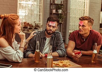 Attractive friends enjoying time while playing a hedbanz game together.
