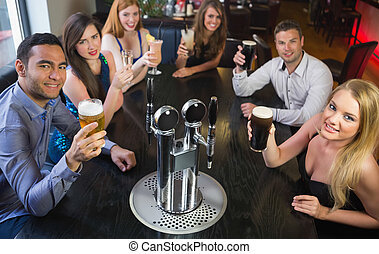 Attractive friends raising glasses up smiling at camera